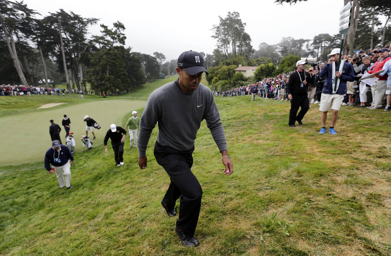Tiger Woods trudges up a hill off the 18th green Wednesday during a practice round for the U.S. Open at the Olympic Club, a course that was essentially built on the side of a giant sand dune that leads toward Lake Merced.