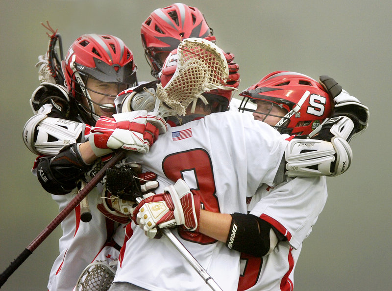 John Wheeler, center front, celebrates with his teammates after scoring just before the end of the first half Wednesday night against Kennebunk in the Western Class A boys' lacrosse championship game. Wheeler finished with three goals and an assist as Scarborough won, 6-3.