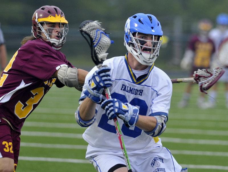 Jack Cooleen of Falmouth prepares to pass while taking a hit from Adam Haversat of Cape Elizabeth during Falmouth's 10-9 victory in the Western Class B final Wednesday night.