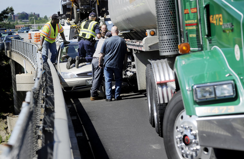 Crews work to remove a car that was wedged between a tractor-trailer and the guardrail on Interstate 295's northbound lanes in Portland on Thursday morning. The vehicles crashed in an area that is under construction. Northbound traffic was detoured at Exit 4 at the Veterans Memorial Bridge while the accident was cleared.