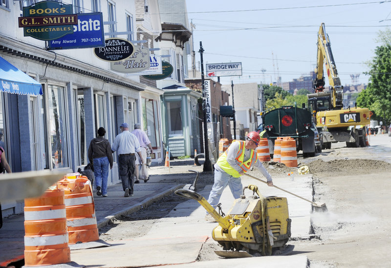 Mike Stuart of Shaw Brothers Construction cleans up in the construction zone Thursday as pedestrians walk along the sidewalk on Ocean Street in Knightville. The work began in April and is expected to continue through October.