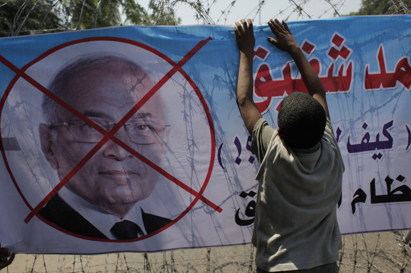 """An Egyptian youth hangs a banner with a defaced picture of presidential candidate Ahmed Shafiq and Arabic that reads """"Shafiq, the former regime,"""" in Cairo, Egypt, Thursday."""