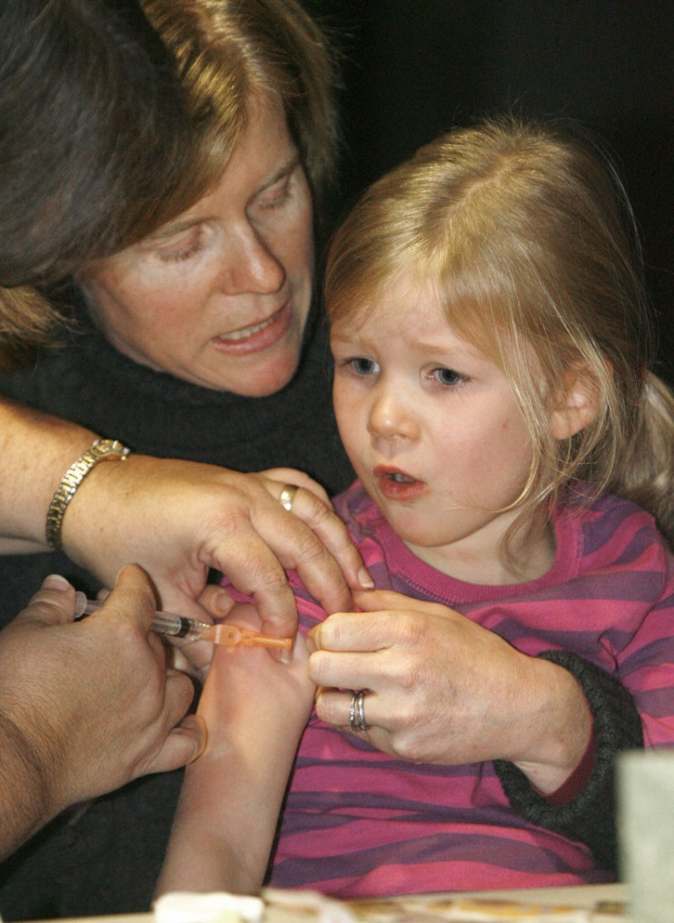 A mother holds her daughter as she awaits a flu shot in Duxbury, Vt., in 2009. In Maine, more than 226,000 people received immunizations and other preventive care services over the last year with no out-of-pocket costs, thanks to the Affordable Care Act, two legislators say.
