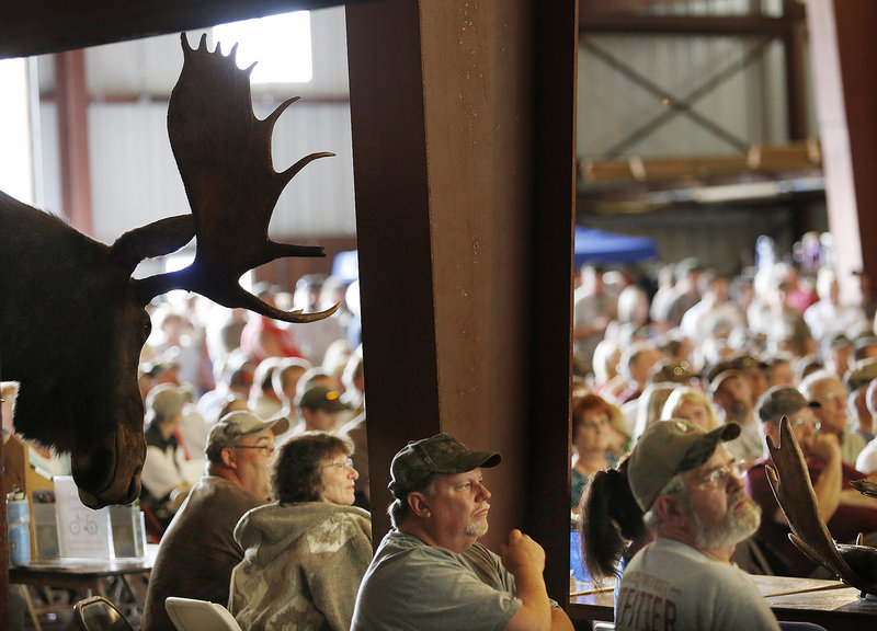 People listen for their names to be called during the moose lottery in Oquossoc on Saturday. Officials said it was the biggest festival ever held in the region.