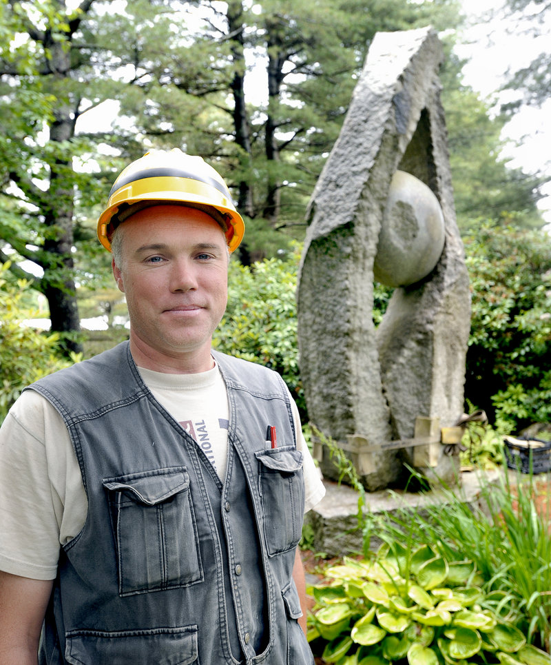 "Sculptor Jesse Salisbury stands in front of ""Tidal Moon,"" his 14-foot granite artwork, as it was being readied for transport last Saturday from the Yarmouth residence of William and Mary Louise Hamill."