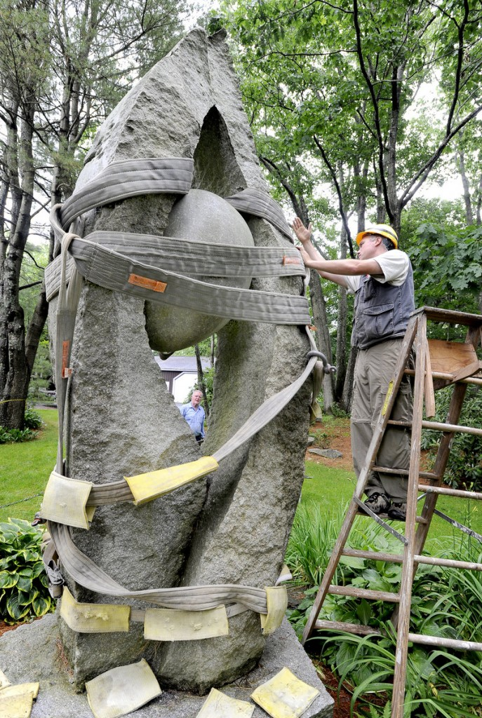 "Jesse Salisbury prepares his granite sculpture ""Tidal Moon"" for its trip from the Yarmouth residence of William and Mary Louise Hamill to the Portland International Jetport where it will be displayed near the terminal's baggage claim entrance."