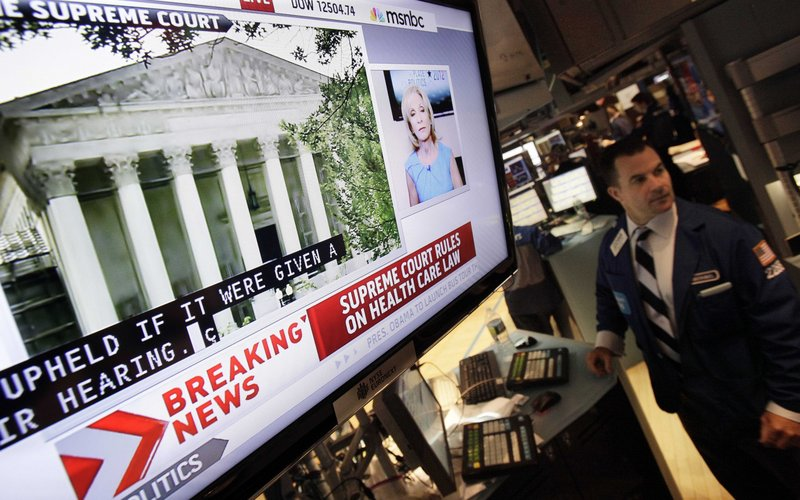 A television screen at a trading post on the floor of the New York Stock Exchange headlines the Supreme Court decision on health care Thursday.