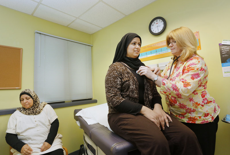 Patricia McGargill, a nurse practitioner at Portland Community Health Center, tends to Maha Dawood, 18, of Portland while her mother Fadeela Maykha waits Thursday.