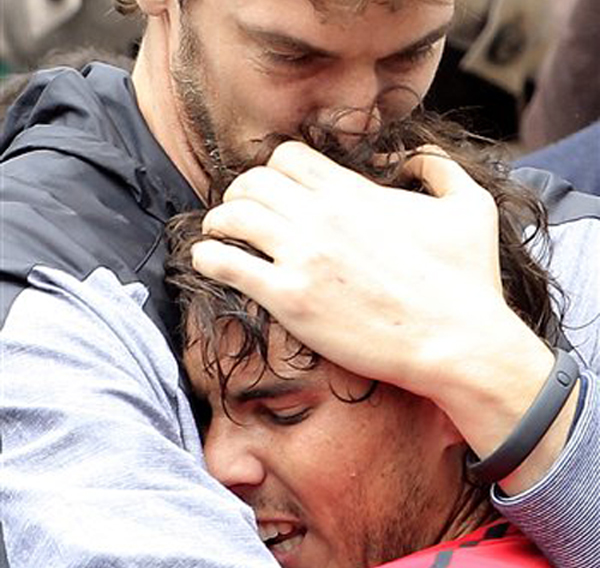 Spanish NBA player Pau Gasol, top, hugs compatriot and friend Rafael Nadal after Nadal defeated Serbia's Novak Djokovic in their men's final match in the French Open in Paris today.