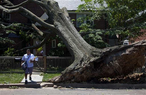 Giovanny Alvarez, a letter carrier for the U.S. Postal Service, delivers mail in Washington Monday, where a powerful storm swept through the region on Friday.