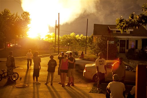 People watch flames shoot up from a freight train that derailed and some cars burst into flames, early this morning in Columbus Ohio. The accident happened at about 2 a.m. in a mixed-use part of the city, and people living within a one-mile radius of the blast were evacuated.