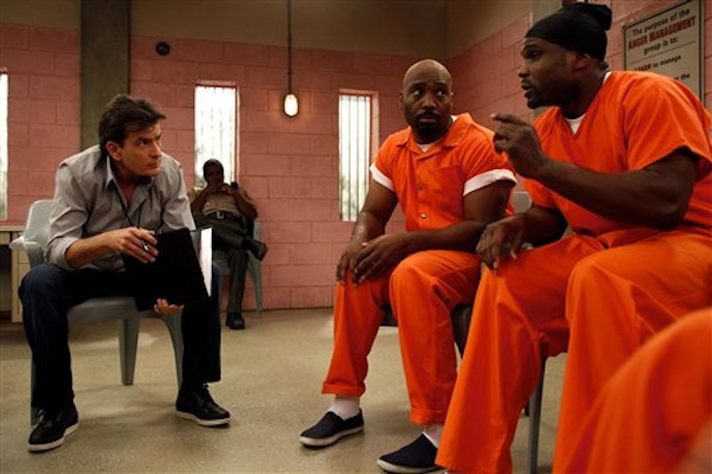 This publicity image released by FX shows Charlie Sheen, left, with James Black and Darius McCrary, right, in a scene from the new comedy