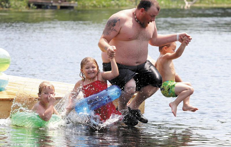 Jason Madore of Vassalboro jumps off a floating swim dock with three of his kids while cooling off in the middle of Outlet Stream in North Vassalboro on Sunday. From left to right are Jayden Madore, 5, Miah Deckard, 5, and Kendrick Williamson, 4.