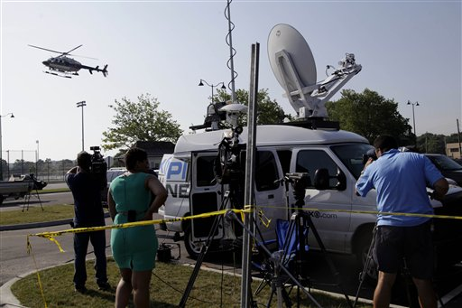 Reporters watch as a police helicopter lands today at a staging area for an investigation into the fatal yacht capsize in Oyster Bay, N.Y.