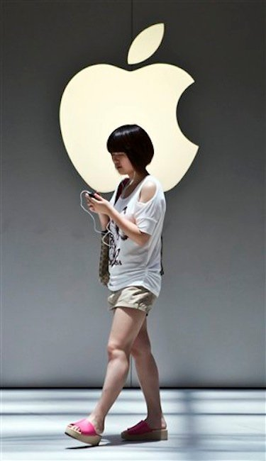A woman walks near the Apple logo outside an Apple store in Shanghai, China on Monday July 2, 2012. Apple agreed to pay $60 million to settle a dispute in China over ownership of the iPad name, a court announced Monday, removing a potential obstacle to sales of the popular tablet computer in the key Chinese market. (AP Photo)