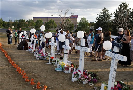 People visit a memorial for the victims in the shooting across the street from the Century 16 movie theater in Aurora, Colo., on Sunday.