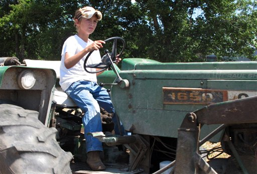 Jacob Mosbacher, 10, drives a tractor through a bean field on his grandparents' property near Fults, Ill., recently. Agriculture organizations and federal lawmakers from farm states succeeded last spring in convincing the U.S. Labor Department to drop proposals limiting farm work by children such as Jacob, whose parents say such questions of safety involving kids should be left to parents.