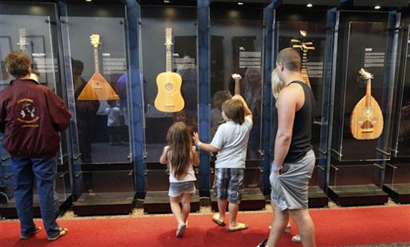 In this Tuesday, June 26, 2012 photo, visitors walk by the display of the instruments that is part of the touring National Guitar Museum exhibit on display at the Carnegie Science Center in Pittsburgh, through Sept. 30, 2012. The National Guitar Museum is a traveling guitar museum searching for a home. Museum director HP Newquist said the initial plan was to take it on the road for five years, to find out which city was the most hospitable. The museum is on a nine-city tour. (AP Photo/Keith Srakocic)