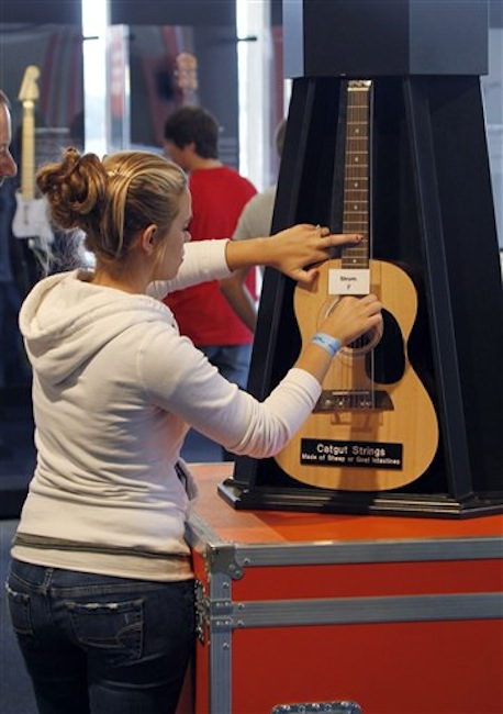 In this photo made on Tuesday, June 26, 2012, Courtney Dusseau, of Monroe, Mich., strums on an acoustic guitar strung with catgut strings that is part of the touring National Guitar Museum exhibit on display at the Carnegie Science Center in Pittsburgh, through Sept. 30, 2012. The National Guitar Museum is a traveling guitar museum searching for a home. Museum director HP Newquist said the initial plan was to take it on the road for five years, to find out which city was the most hospitable. The museum is on a nine-city tour. (AP Photo/Keith Srakocic)