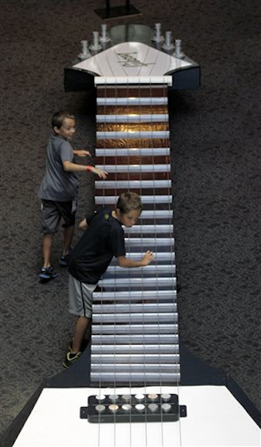 In this photo made on Tuesday, June 26, 2012, 10-year-old Ian Solorzano, bottom, and his brother Logan Solorzano, 8, play with the strings on the neck of the 40-foot long working model of a 1957 Gibson Flying V electric guitar that is part of the touring National Guitar Museum exhibit on display at the Carnegie Science Center in Pittsburgh, through Sept. 30, 2012. (AP Photo/Keith Srakocic)