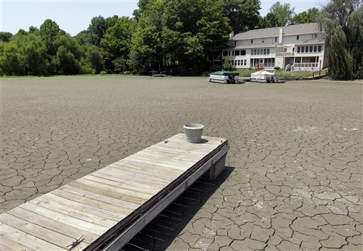 A dock extends into a dry cove at Morse Reservoir in Noblesville, in central Indiana, where temperatures exceeded 100 degrees Thursday. The reservoir is down 3.5 feet from normal levels.
