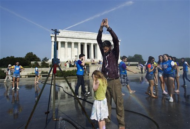 Visitors get much needed relief from a water sprinkler set up at the National Mall near the Lincoln Memorial, rear, in Washington Saturday, July 7, 2012. The heat gripping much of the country is set to peak Saturday in many places, including some Northeast cities, where temperatures close to or surpassing 100 degrees are expected. (AP Photo/Manuel Balce Ceneta)