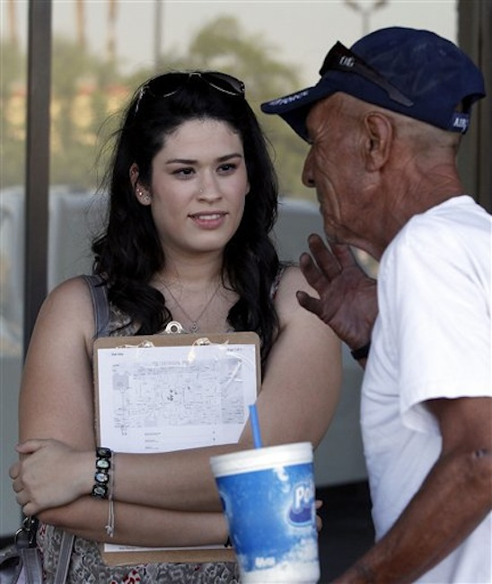 In this Friday, June 29, 2012 photo, Carissa Valdez, left, a volunteer for President Barack Obama's reelection campaign, listens to Ruben Gallardo, who she registers to vote, as a group of volunteers work to register new voters as they canvass a heavily Latino neighborhood in Phoenix. Across the country both political parties have been courting the Latino vote, the nation's fastest-growing minority group. (AP Photo/Ross D. Franklin)