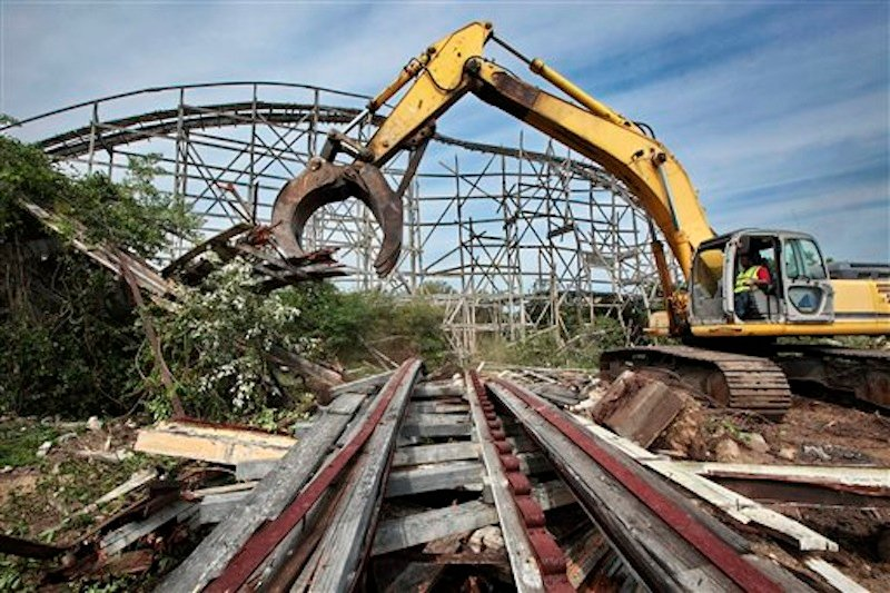 Earl Thibeault powers a machine as he demolishes the Comet roller coaster at the defunct Lincoln Park amusement park in Dartmouth, Mass., Wednesday July 11, 2012. The crumbling roller coaster is being cleared for a development that will include single-family homes, apartments and commercial space. (AP Photo/The Standard-Times, Peter Pereira) entertainment;coaster;roller coaster;wooden;fun;demolition