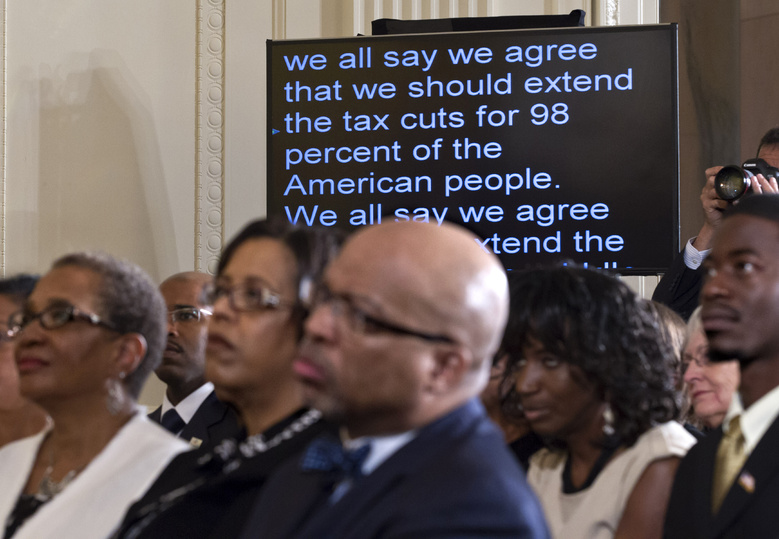 President Barack Obama's speech on extending tax cuts for the middle class scrolls past on a monitor as the audience listens in the East Room of the White House in Washington on Monday.