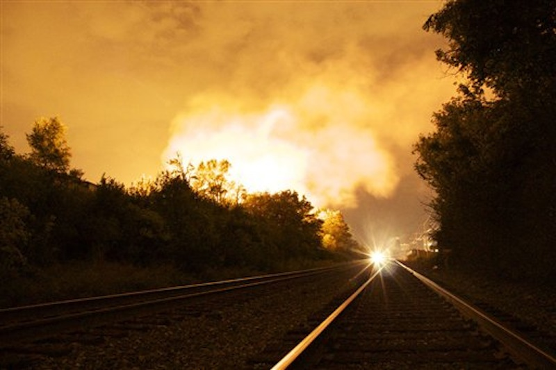 Flames rise from a derailed freight train, left unseen, early Wednesday July 11, 2012 in Columbus Ohio. Part of a freight train derailed and caught fire in Ohio's capital city early Wednesday, shooting flames skyward into the darkness and prompting the evacuation of a mile-wide area as firefighters and hazardous materials crews worked to determine what was burning and contain the blaze.(AP Photo/Chris Mumma)
