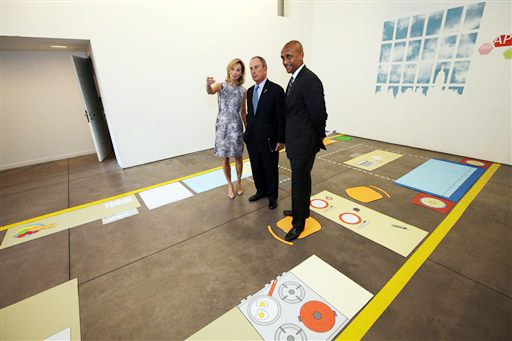 New York City Mayor Michael Bloomberg, center, stands with Amanda Burden, left, Department of City Planning Director, and Commissioner Mathew Wambua, Department of Housing Preservation and Development, in the kitchenette area of a full-scale mockup of a 300-square-foot apartment.