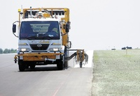 A truck paints the edge of the newly repaved runway that reopened on Friday at the Augusta State Airport. The project included narrowing the width of the runway.