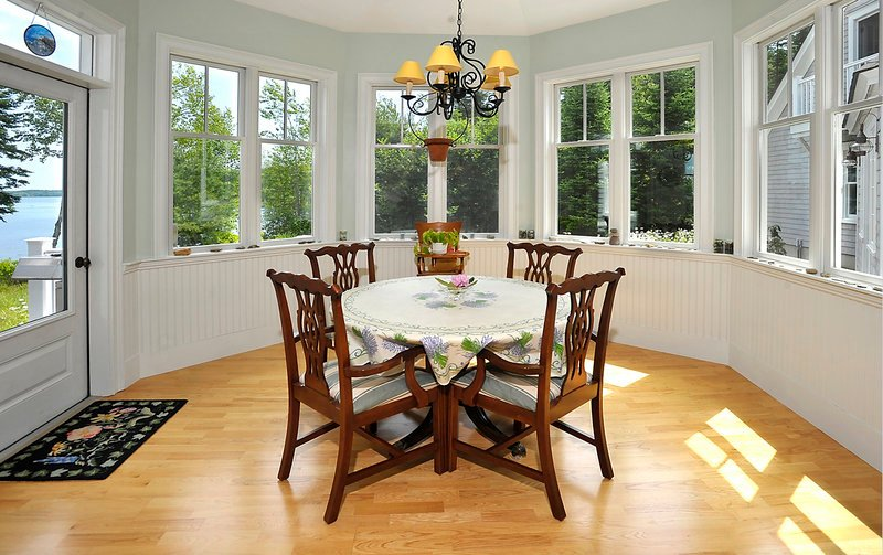 The six-sided room off the kitchen, with views of woods and water, serves as a breakfast room.