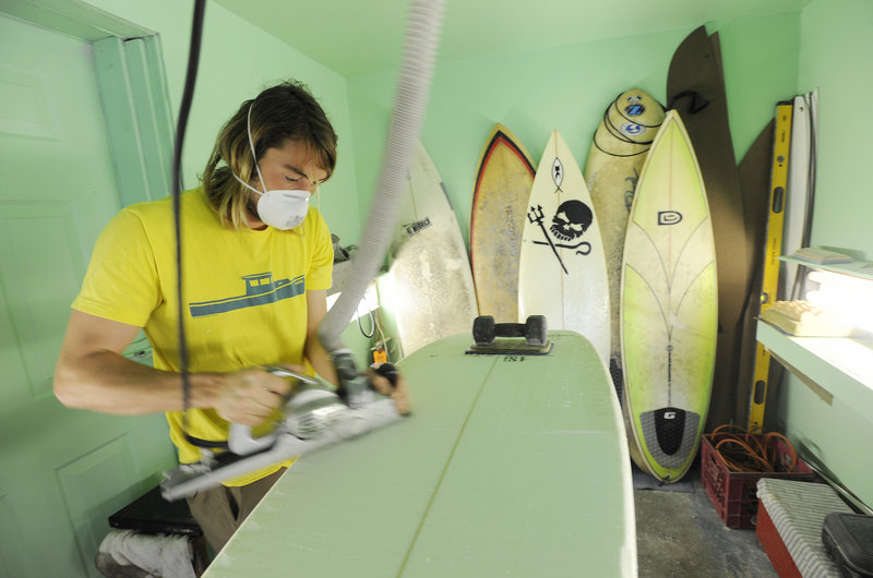 Andy McDermott, 28, shapes a board at Black Point Surf Shop.