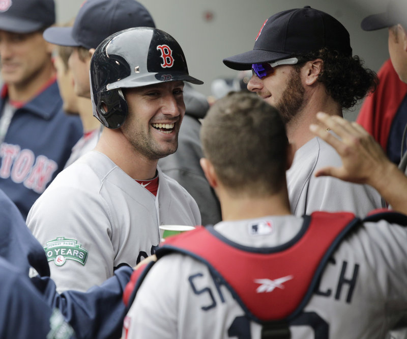 Ryan Kalish joins a happy Boston dugout after scoring the eventual winning run in the 10th inning on a sacrifice fly by David Ortiz at Seattle on Sunday.