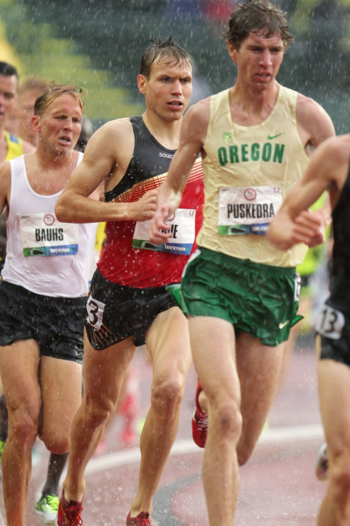 Ben True, in red and black, runs in the rain in the 10K at the Olympic trials in Eugene, Ore. He placed 12th in that race and 6th in the 5K finals.