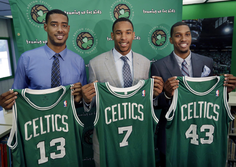 Boston Celtics 2012 draft picks, from left, center Fab Melo and forwards Jared Sullinger and Kris Joseph hold up their jerseys during an introductory NBA basketball news conference in Boston on Monday.