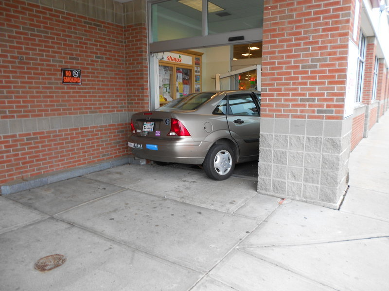 "A 2003 Ford Focus sits in the entrance of the Shaw's Supermarket on Scammon Street. ""We were very lucky today"" because no one was hurt, said police Sgt. Christopher Hardiman."