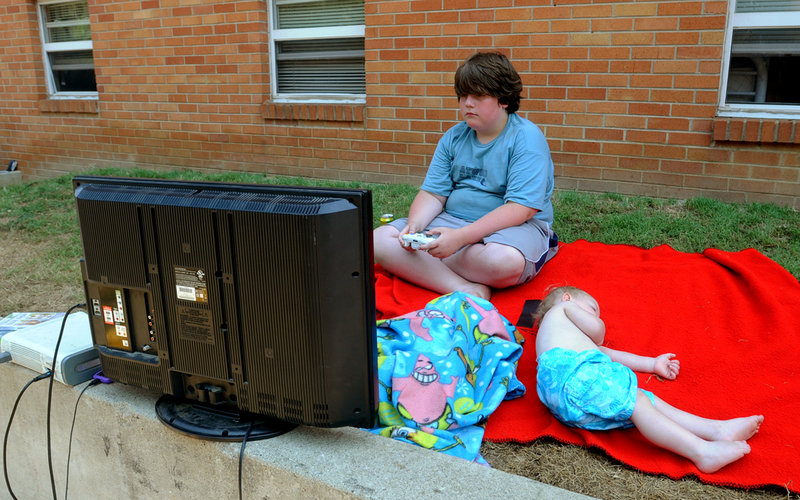 Derek Longo, 11, plays a video game, powered by a running car engine hooked up to a power inverter, outside his home at Bruce Apartments in Ashland, Ky. Sleeping on the ground next to him Monday as they wait for the power to be restored is Joseph DeLong.