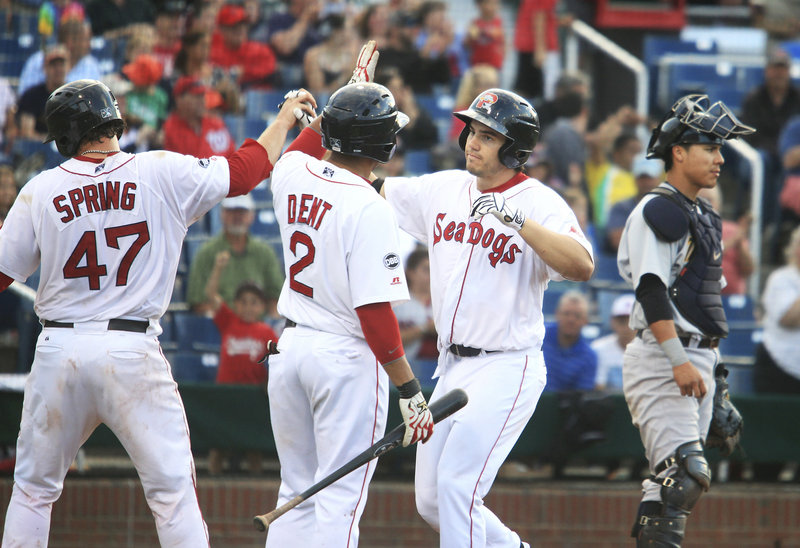 Sea Dog Drew Hedman, center, is congratulated by Matt Spring and Ryan Dent after his three-run home run in the bottom of the fourth at Hadlock Field on Monday. Portland, however, lost 12-4 in the first game of a doubleheader.