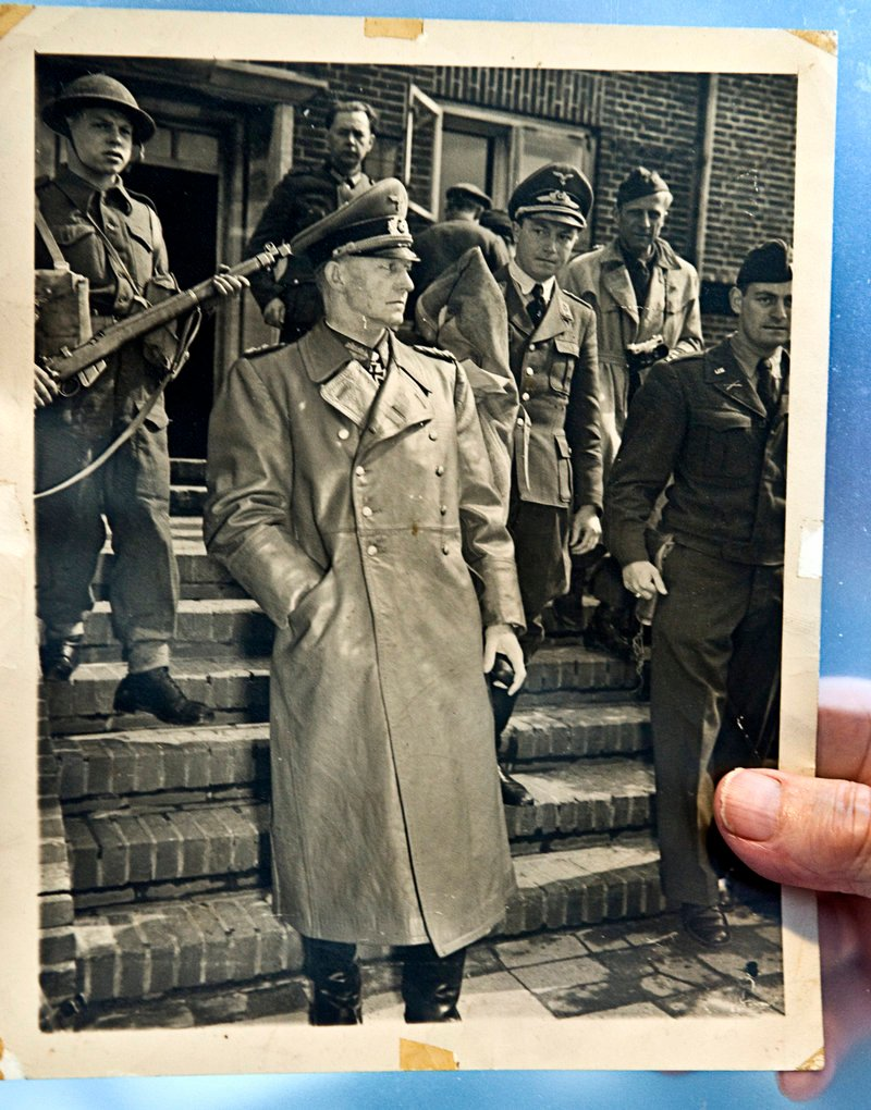 Retired Army Capt. Seymour S. Steinberg holds a photograph from May 1945 showing him, at right, with Nazi officer Alfred Jodl. Steinberg was assigned the task of transporting the top Hitler aide.