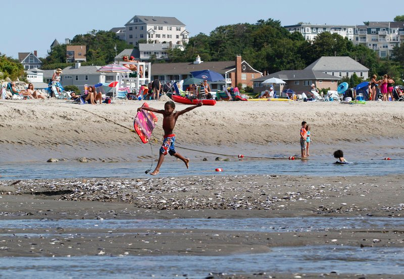 Visitors enjoy the sand and water at Riverside Beach in Ogunquit on Tuesday.