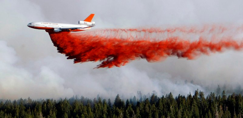 A heavy tanker drops retardant as crews battle the Shingle Fire east of Cedar City, Utah, on Monday. The suspension of the Air Force's C-130 flights Sunday left just 14 such planes in use.
