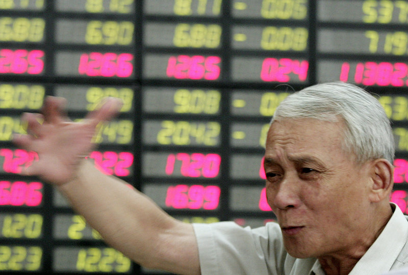 An investor gestures Wednesday in Shanghai, China. Global investors were cautious on a day Wall Street was closed. However, benchmark oil for August delivery was down 66 cents at $87 a barrel in electronic trading.