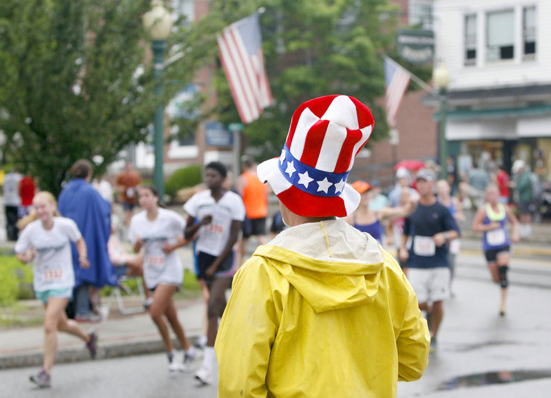 Bill Farrell of Plymouth, Mass., watches runners turn onto Depot Street during the Four on the Fourth road race Wednesday in Bridgton. Farrell's son-in-law was competing.