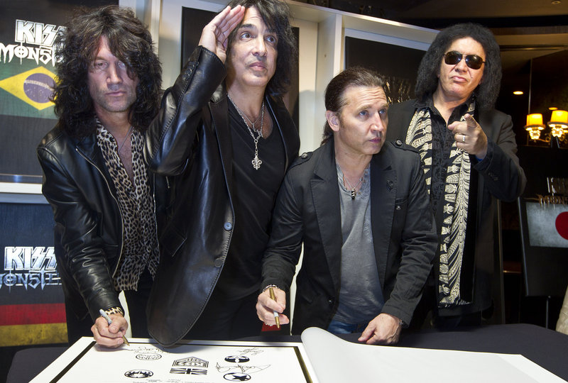 KISS, from left, Tommy Thayer, Paul Stanley, Eric Singer and Gene Simmons, sign their book Wednesday in London.