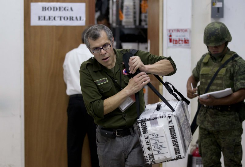An electoral official carries a ballot box Wednesday in Mexico City. With 99 percent of the vote tallied in the preliminary count, Enrique Pena Nieto of the PRI, led with 38 percent of the vote in the presidential election.