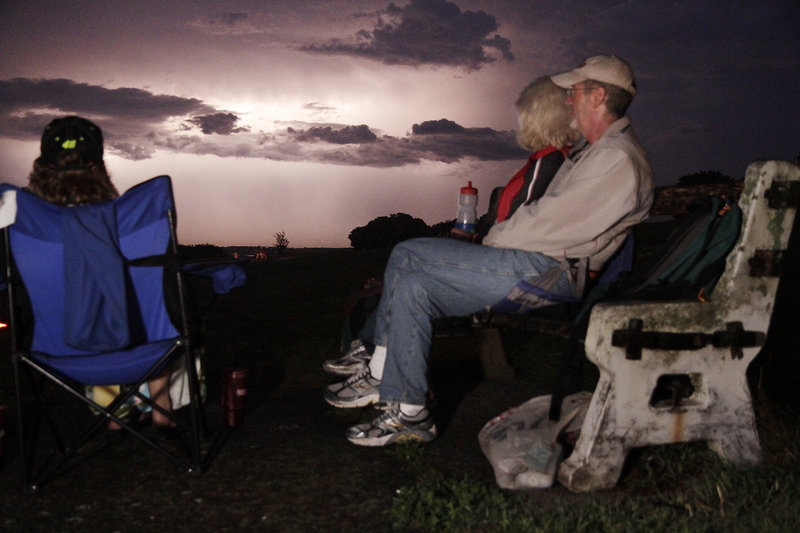 Janet Kramlich of Scarborough and Joe and Amy Montefusco of Portland watch a natural light show that brought rain and postponed Fourth of July festivities on Portland's Eastern Prom.