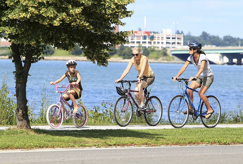 Kendra Drinkwater, right, her daughter, Sage, 9, and her mother, Paula Marquis of Portland, do some biking Thursday along Back Cove in Portland.