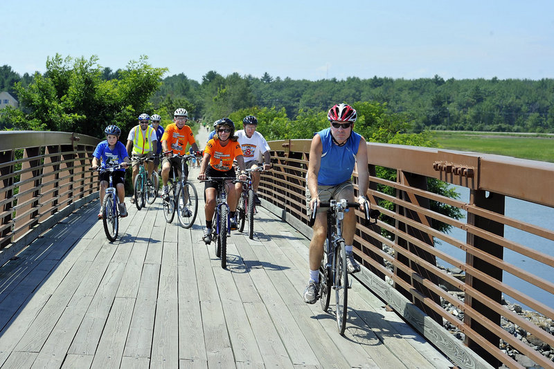 Dan Stewart, right, bicycle and pedestrian program manager for the Maine Department of Transportation, leads cyclists over the Eastern Trail bridge at Scarborough Marsh last summer. Stewart said it is premature to say how state programs will be affected by cuts proposed in a new $120 billion federal transportation plan.